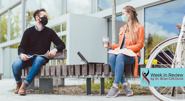 man and women on bench in masks