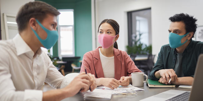 people wearing masks in a meeting